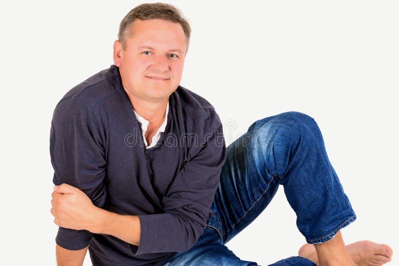 Niezobowiązująco ubierający w średnim wieku mężczyzna na podłoga zdjęcia stock