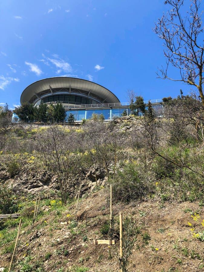 Niezwykły futurystyczny round budynek w postaci latającego spodeczka na górze zielonego wzgórza z trawą i krzakami zdjęcia royalty free