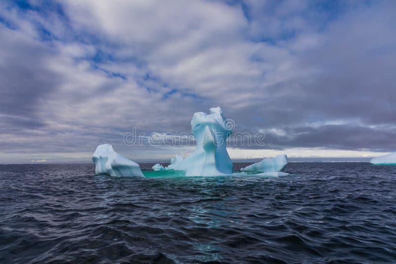 Niezwykle kształtna góra lodowa unosi się w morzu przeciw błękitnemu i chmurnemu niebu, Antarctica obrazy royalty free