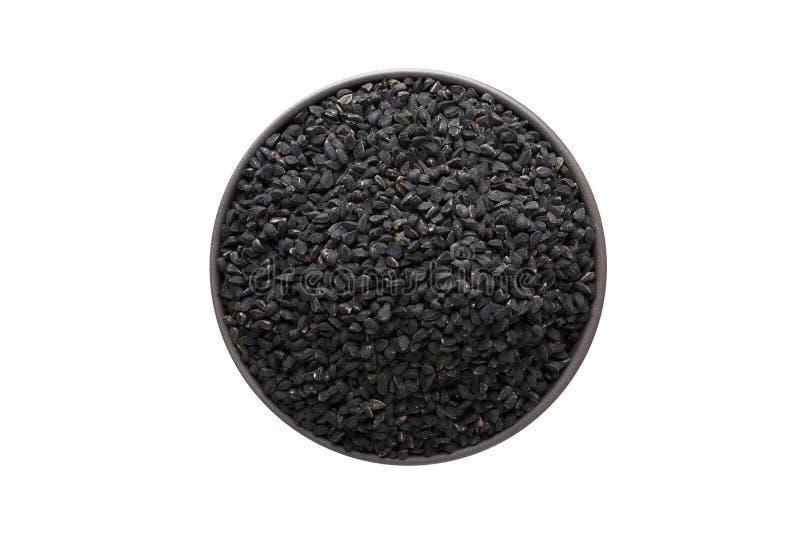 Nigella или черные семена тимона в шаре глины изолированном на белой предпосылке Взгляд сверху приправой или специей стоковые фото