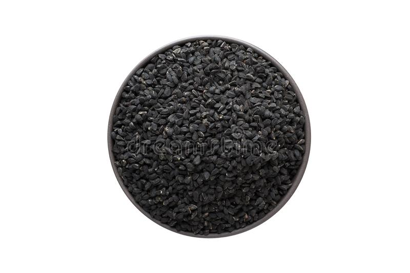Nigella or Black cumin seeds in clay bowl isolated on white background. Seasoning or spice top view stock photos