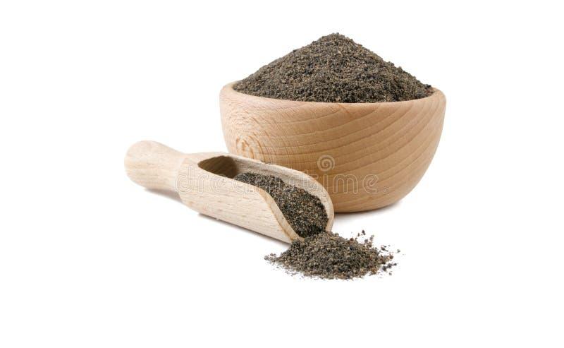 Nigella moído ou moído na bacia de madeira e na colher isoladas no fundo branco Especiarias e ingredientes de alimento foto de stock