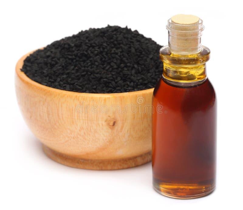 Nigella sativa eller svart spiskummin med nödvändig olja royaltyfri foto