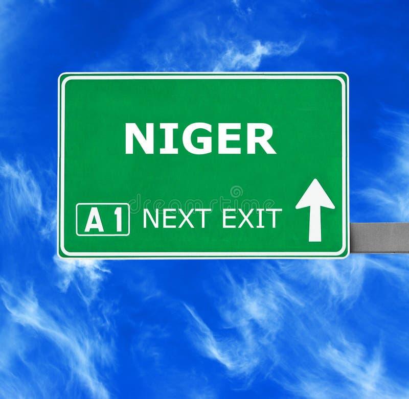 Niger drogowy znak przeciw jasnemu niebieskiemu niebu zdjęcia stock