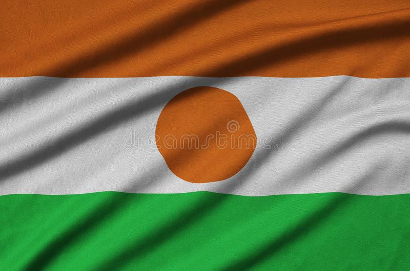 Niger flag is depicted on a sports cloth fabric with many folds. Sport team banner. Niger flag is depicted on a sports cloth fabric with many folds. Sport team stock photos