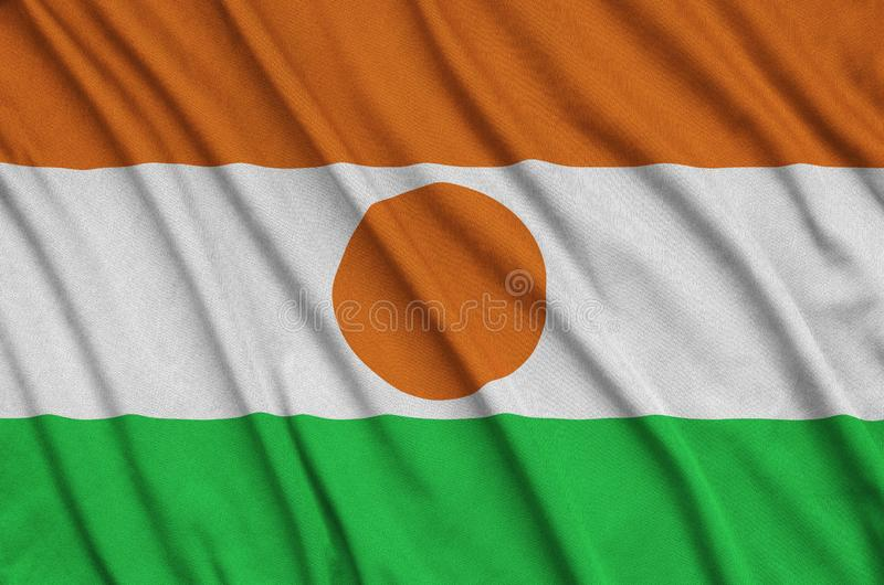 Niger flag is depicted on a sports cloth fabric with many folds. Sport team banner. Niger flag is depicted on a sports cloth fabric with many folds. Sport team stock images