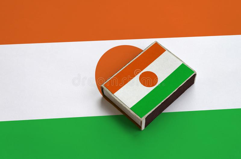 Niger flag is pictured on a matchbox that lies on a large flag.  stock image