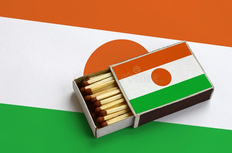 Niger flag is shown in an open matchbox, which is filled with matches and lies on a large flag.  stock photo