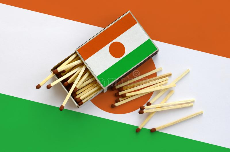 Niger flag is shown on an open matchbox, from which several matches fall and lies on a large flag.  stock image