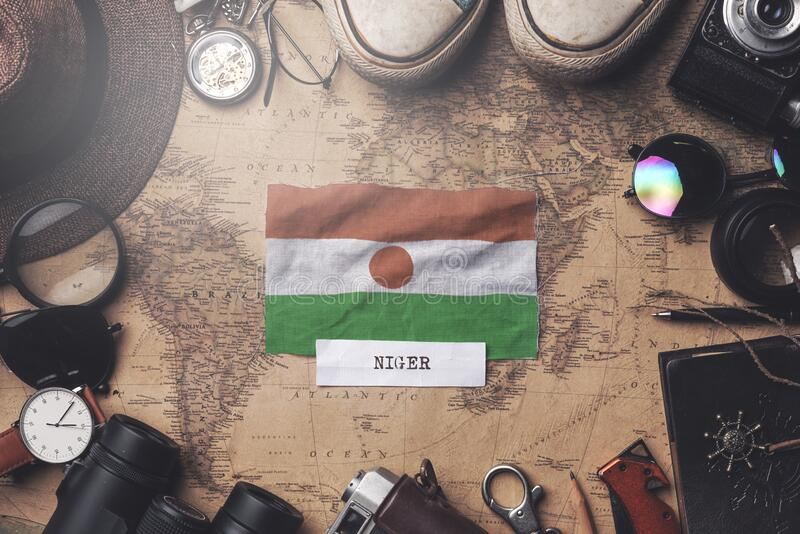 Niger Flag Between Traveler`s Accessories on Old Vintage Map. Overhead Shot royalty free stock photos