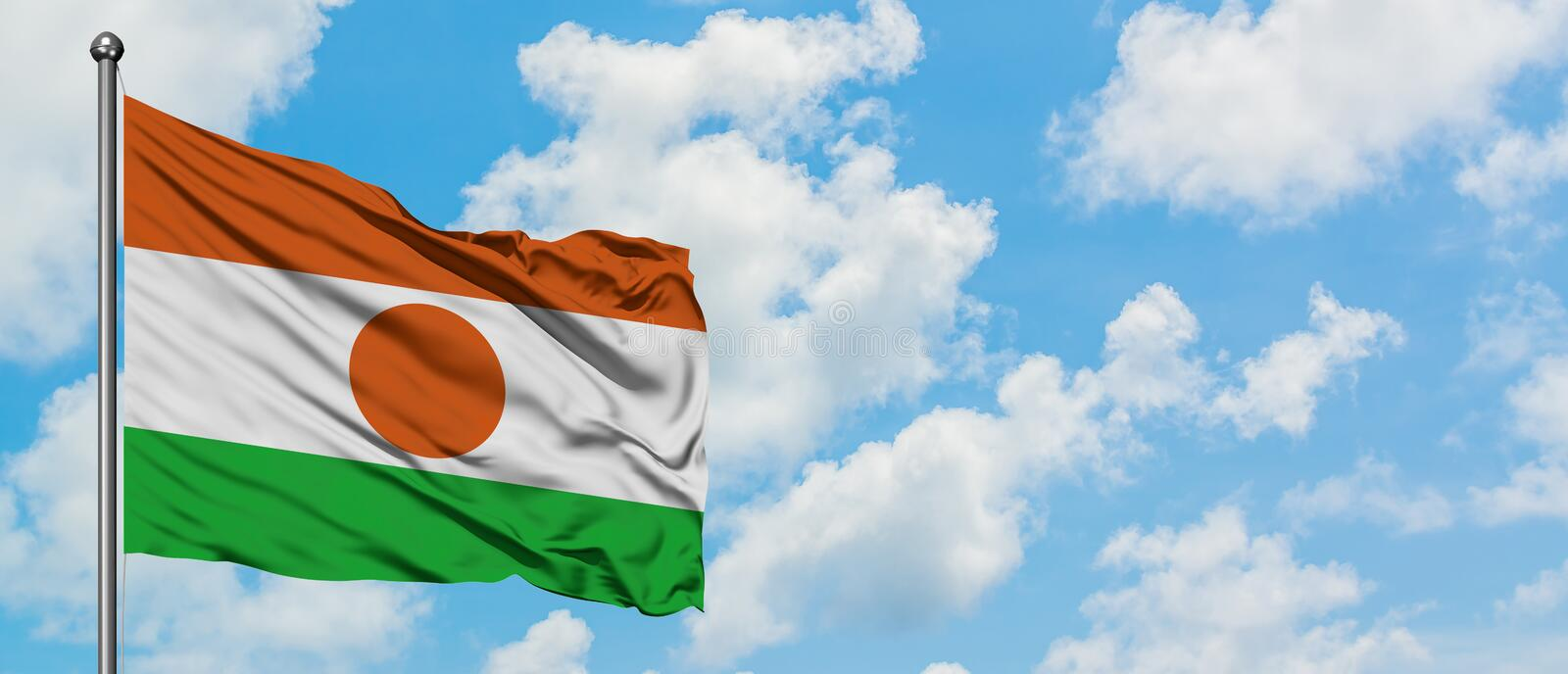 Niger flag waving in the wind against white cloudy blue sky. Diplomacy concept, international relations.  royalty free stock photography