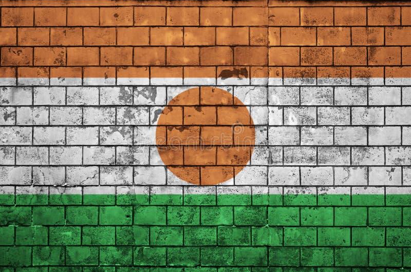 Niger flaga maluje na starym ściana z cegieł fotografia royalty free