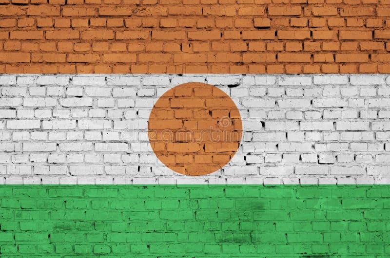 Niger flaga maluje na starym ściana z cegieł zdjęcie royalty free