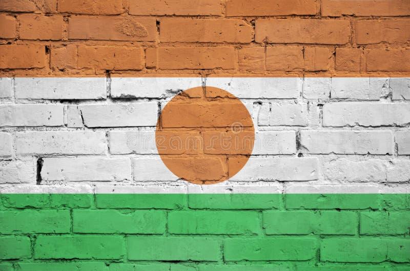 Niger flaga maluje na starym ściana z cegieł zdjęcie stock