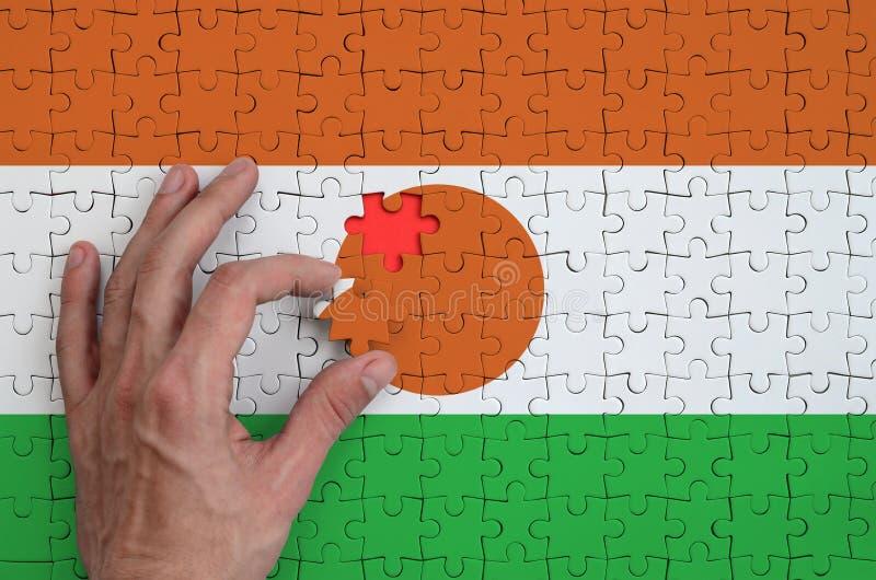 Niger flaga przedstawia na łamigłówce którą składać uzupełnia mężczyzna ` s ręka, fotografia stock