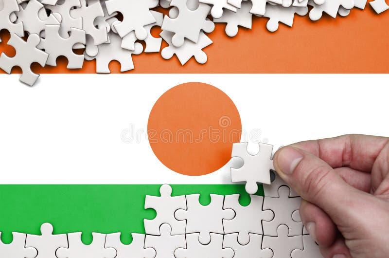 Niger flaga przedstawia na stole na którym składa łamigłówkę biały kolor ludzka ręka obraz royalty free