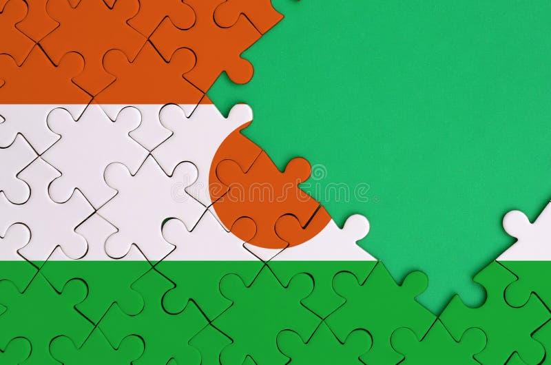 Niger flaga przedstawia na uzupełniającej wyrzynarki łamigłówce z bezpłatną zieleni kopii przestrzenią na prawej stronie zdjęcia royalty free