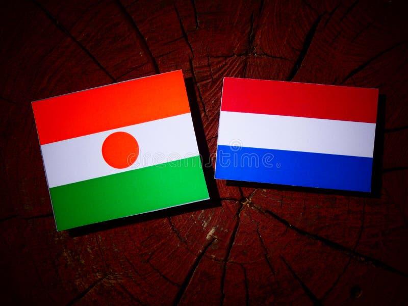 Niger flaga z holender flaga na drzewnym fiszorku odizolowywającym obrazy stock