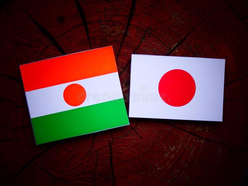 Niger flaga z japończyk flaga na drzewnym fiszorku odizolowywającym zdjęcie royalty free