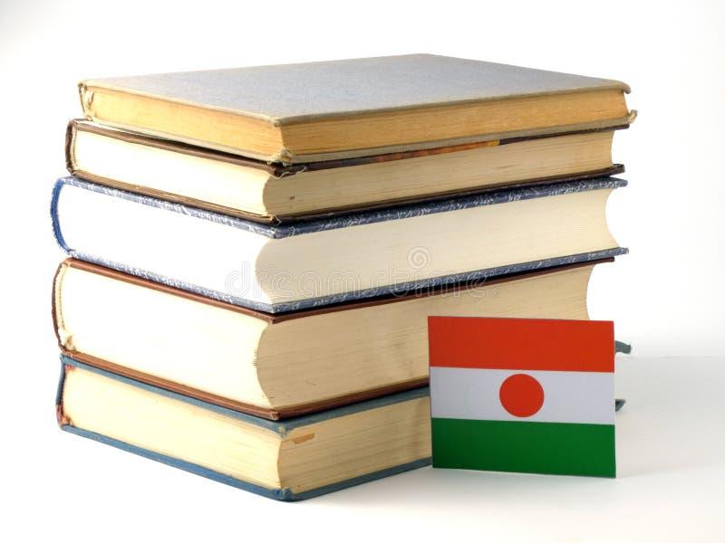Niger flaga z stosem książki na białym tle fotografia stock