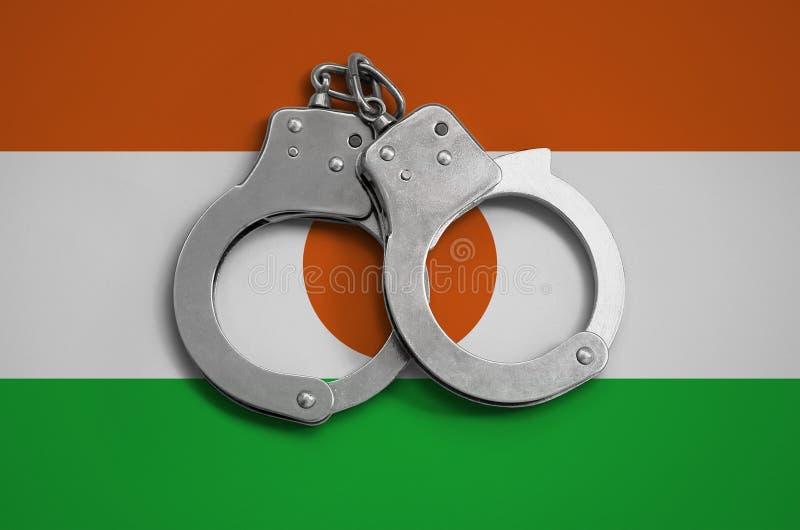 Niger polici i flaga kajdanki Pojęcie święcenie prawo w kraju i ochrona od przestępstwa fotografia royalty free
