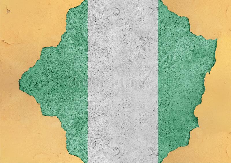 Nigeria flag in big concrete cracked hole and broken material facade. Structure royalty free stock photo