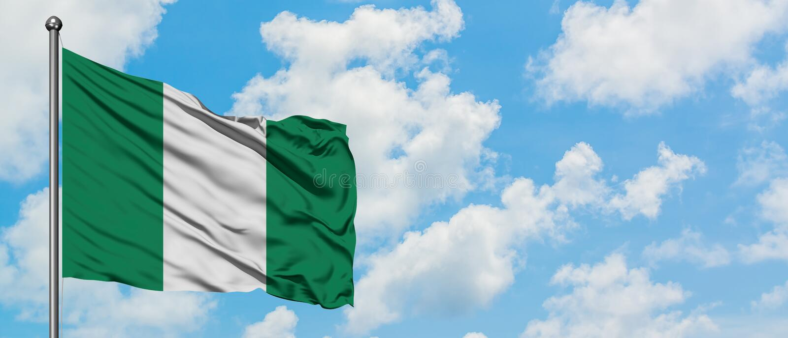 Nigeria flag waving in the wind against white cloudy blue sky. Diplomacy concept, international relations.  royalty free stock image
