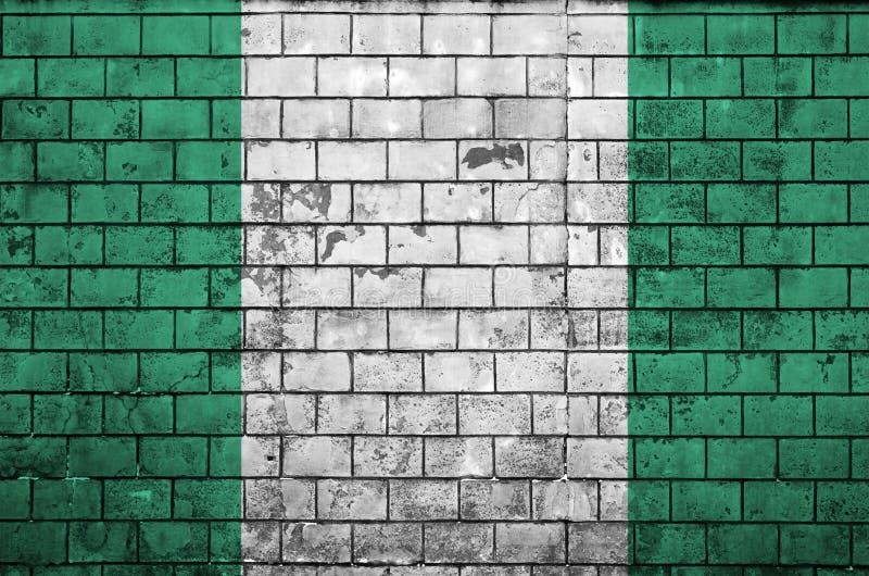 Nigeria flaga maluje na starym ściana z cegieł fotografia stock