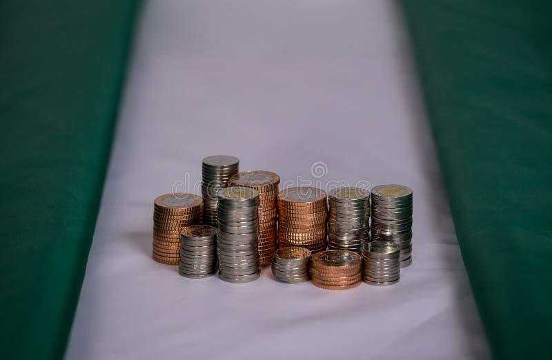 Nigeria-Flagge mit Münzen in einem Stapel lizenzfreie stockfotografie
