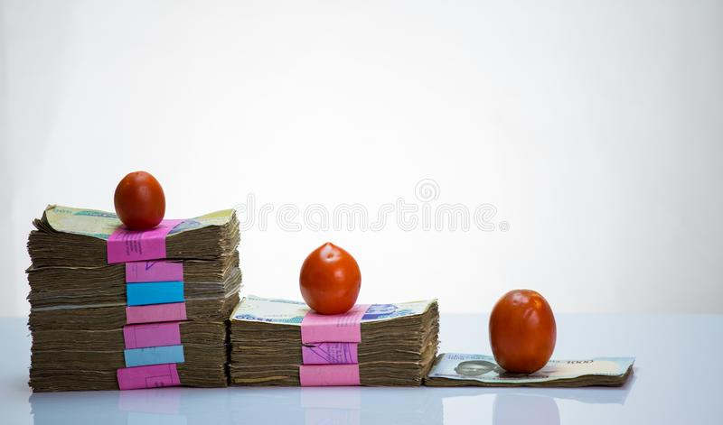 Nigeria local currency N1000, N500,N200 naira notes in a bundleand tomatoes. Prescription bottle with tablets on white background and tomatos and rise in cost of royalty free stock photos