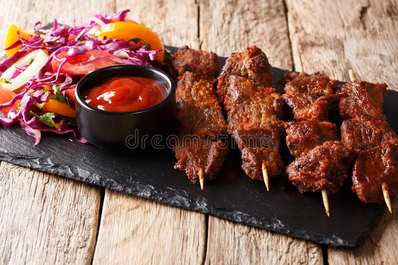 Nigerian barbecue: suya on skewers with fresh vegetable salad an. D ketchup close-up on the table. horizontal stock photos