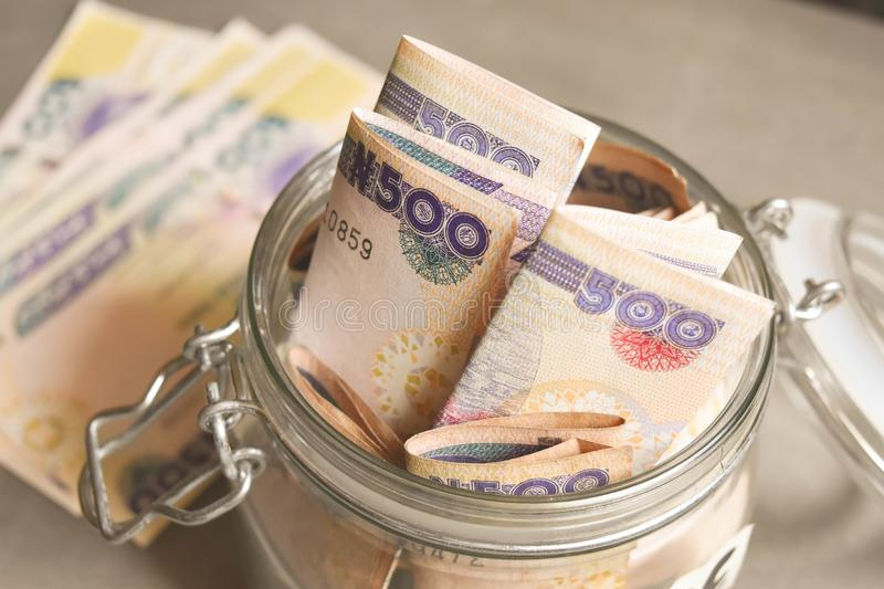 Nigerian Five hundred naira notes in jar for savings concept. Nigerian Five hundred naira notes in jar for savings and investment concept stock image