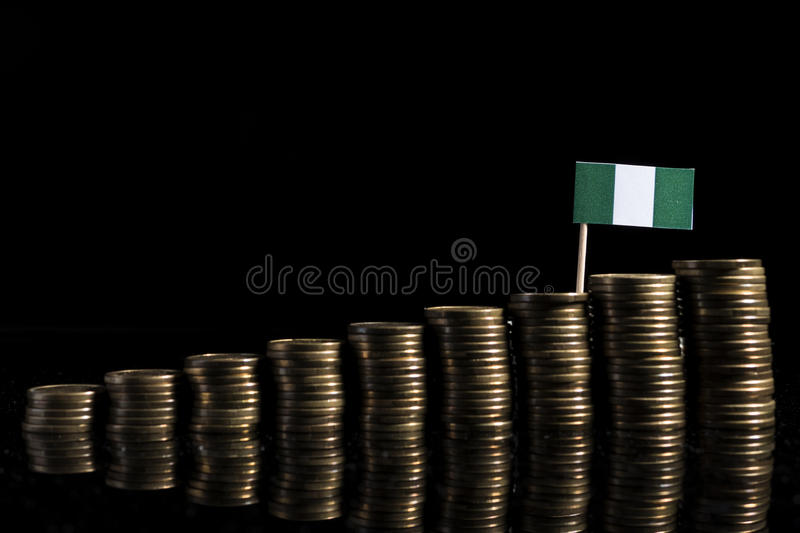 Nigerian flag with lot of coins on black royalty free stock photography