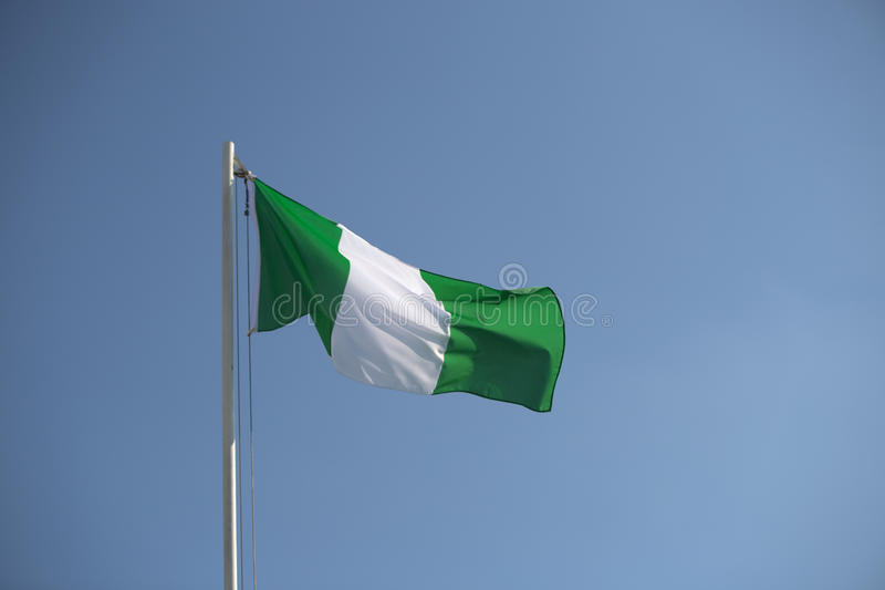 Nigerian flag in the wind. Nigerian flag in front of blue sky in the wind stock photography