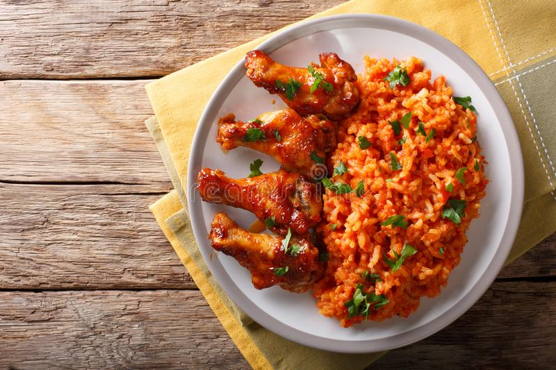Nigerian food party: Jollof rice with fried chicken wings close-up. Horizontal top view. Nigerian food party: Jollof rice with fried chicken wings close-up on a royalty free stock photography