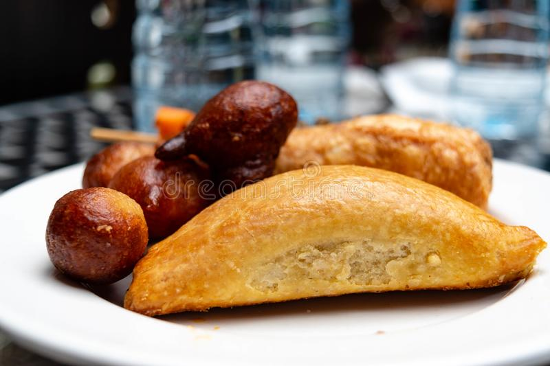 Nigerian meat pie, puff-puff, fish roll and stick meat gizzard pastries or Nigerian small chops in white saucer for Nigerian break. Fast snack or food concept stock photo