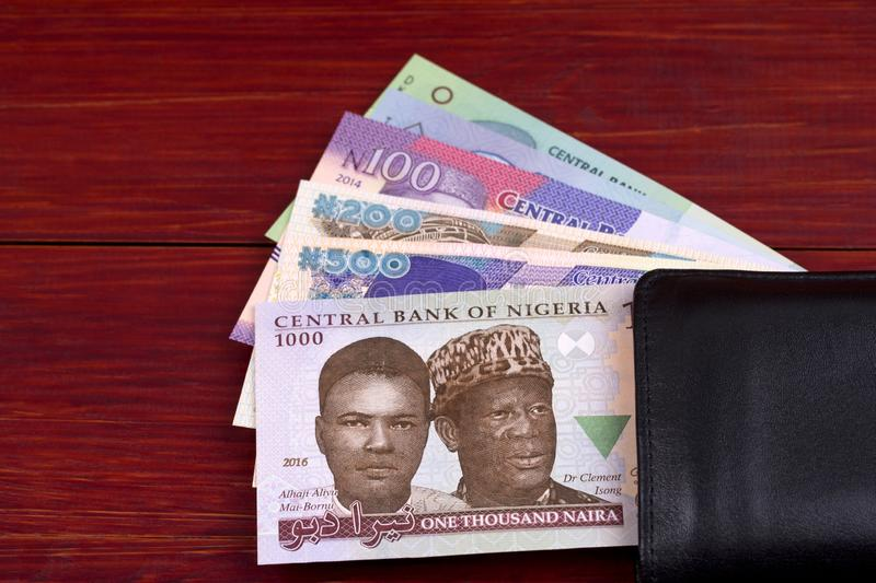 Nigerian Naira in the black wallet. On a wooden background royalty free stock photos