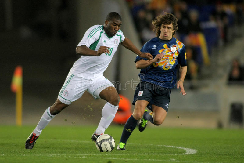 Nigerian player Bright. Fights with Carles Puyol of Catalonia during the friendly match between Catalonia and Nigeria at Estadi Cornella on January 2, 2013 in stock photos