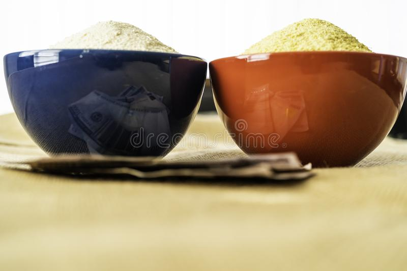 Nigerian yellow and white Garri in Bowls at marketplace. Ready to sell royalty free stock photo
