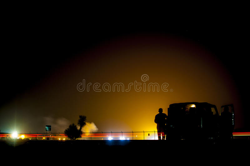 Night Air Show. A plane demonstrates it's acrobatic abilities and lights up fireworks while flying at night. Spectators watch the show royalty free stock image