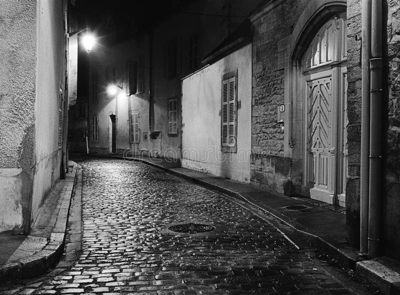 Night Alley In Beaune. A night scene captures an empty alleyway in Beaune, France where the wet cobblestones are shining with lreflected ight from the street stock photo