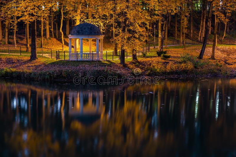 Night in autumn park with pond and rotunda. Night in autumn park with pond and white rotunda royalty free stock images