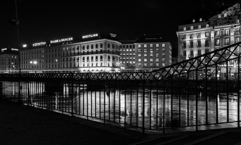 Night black and white cityscape of Geneva. Geneva, Switzerland - November 24, 2016: Night black and white cityscape with illuminated facades and reflections in royalty free stock photos