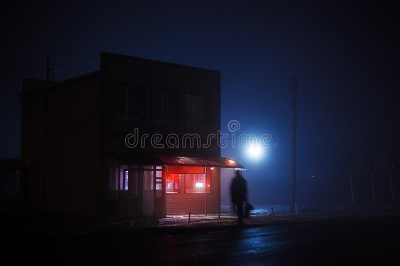 Night blue misty landscape. A small shop with a red illuminated signboard stands on the side of the road, a greasy. Silhouette of a man crosses the road royalty free stock images
