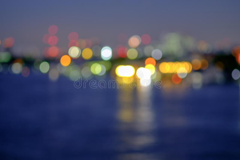 Night blurred lights in city with little light bokeh reflection. Abstract background. Night blurred lights in city with little light bokeh reflection on river stock photo