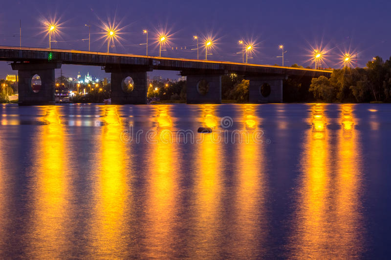 Night bridge lights reflected in river water. HDR. Night bridge lights reflected in river water stock photos