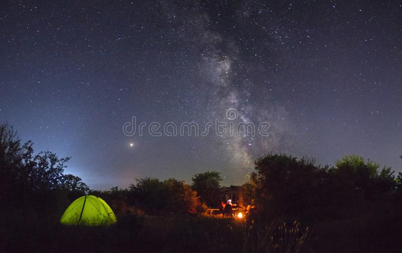 Night camping. Couple tourists have a rest at a campfire near illuminated tent under amazing night sky stock images