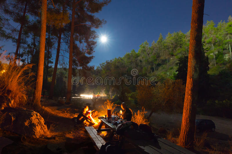 Night camping fire. Group of people camping in forest at night next to fire royalty free stock images