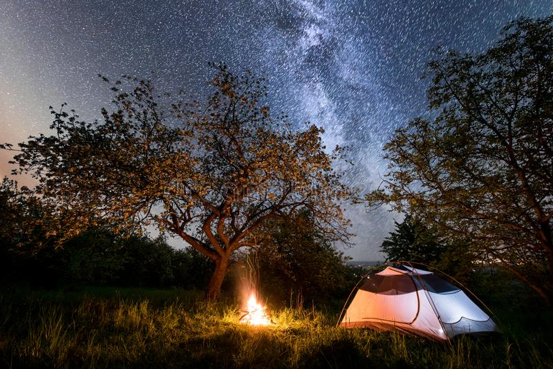 Night camping. tourist tent near campfire under trees and beautiful starry sky and milky way. Night camping. Illuminated tourist tent near campfire under trees royalty free stock image
