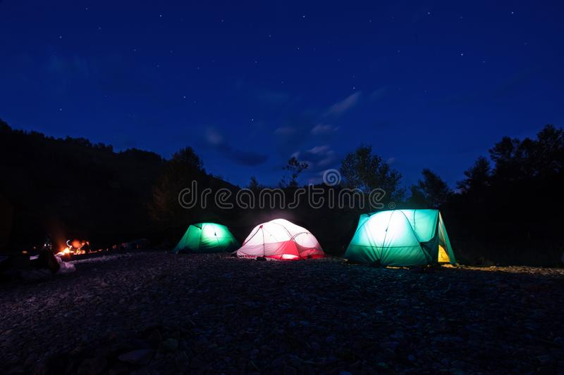 Night camping. Lighted tents and bonfire in the mountains under the night sky with stars. royalty free stock image